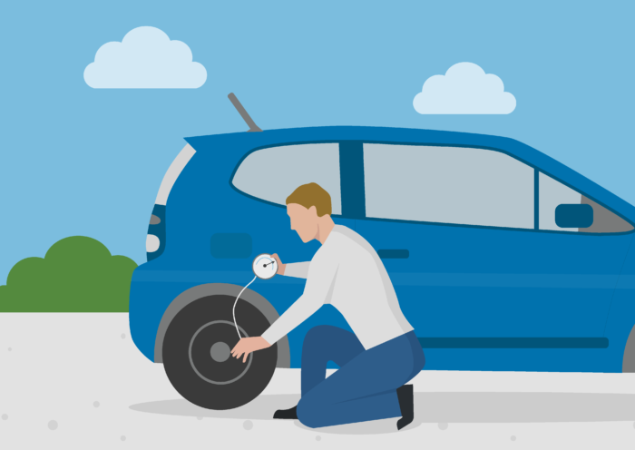 a man checking his tyre pressure to reduce the car's emissions