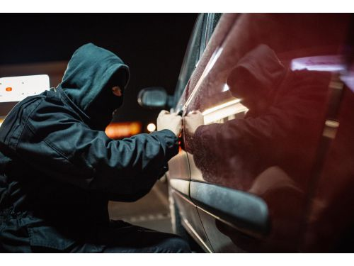 man in a hoodie stealing a car at night