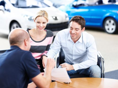 man and woman signing a document to lease their next car